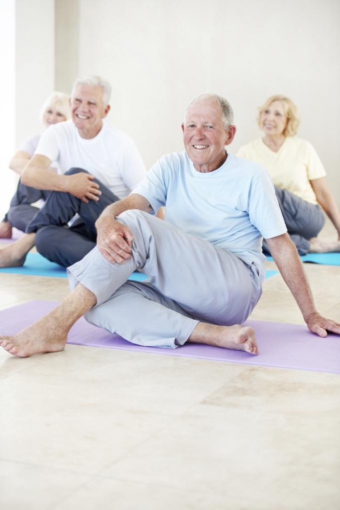 Shot of a senior man enjoying a yoga class with other seniors