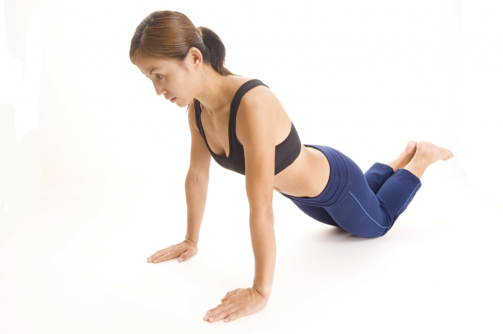 A female fitness instructor demonstrates a close-grip push-up for the triceps