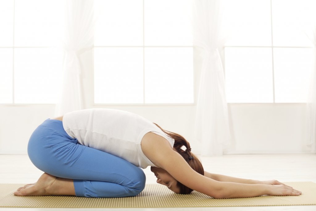 Young woman doing yoga in  Swan Pose (swandasana)