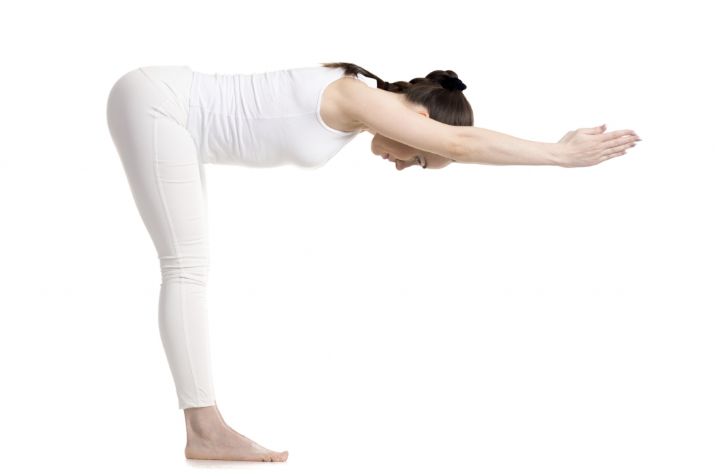 Sporty young beautiful smiling yoga female student in white sportswear doing variation of Standing Half Forward Bend, Ardha Uttanasana pose with stretched hands, studio full length shot, isolated