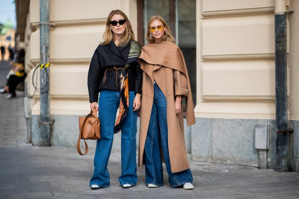 STOCKHOLM, SWEDEN - AUGUST 29: Annabel Rosendahl wearing a brown bag, Loewe scarf, denim jeans and Tine Andrea wearing brown coat, denim jeans seen during Stockholm Runway SS19 on August 29, 2018 in Stockholm, Sweden. (Photo by Christian Vierig/Getty Images)
