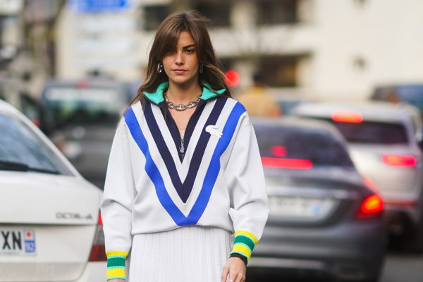 PARIS, FRANCE - MARCH 03: Clara Berry wears a blue black and white striped v-neck Lacoste pullover with colored cuffs, a white pleated skirt, outside Lacoste, during Paris Fashion Week - Womenswear Fall/Winter 2020/2021 on March 03, 2020 in Paris, France. (Photo by Edward Berthelot/Getty Images)